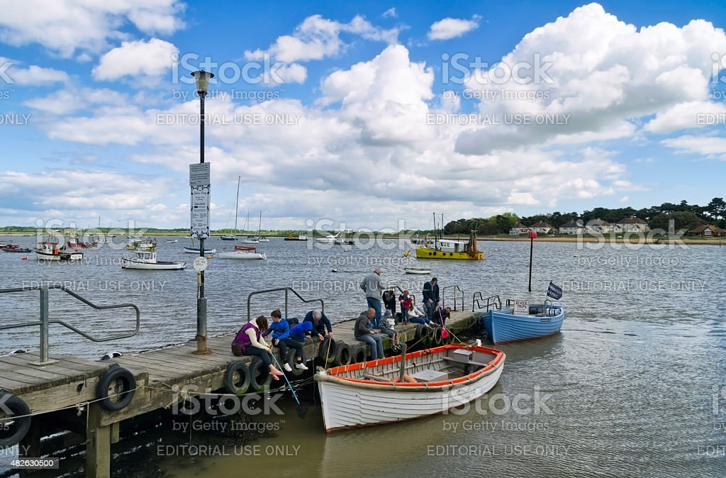 Adults and children fishing from a jetty stock photo