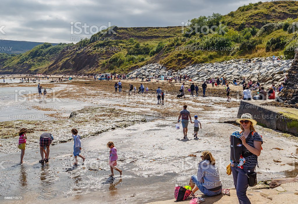 adults and children on the beach and in the sea stock photo