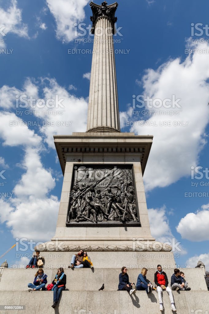 Adults and children rest at the base of the Nelson column stock photo