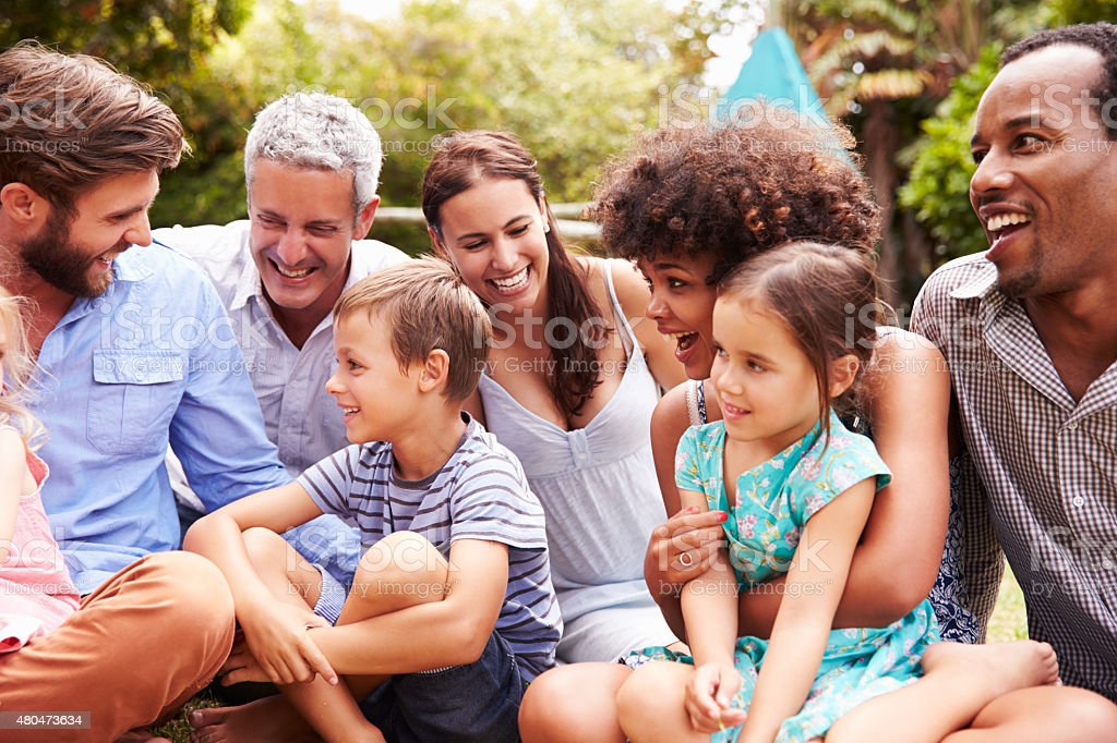 Adults and kids sitting on the grass in a garden stock photo