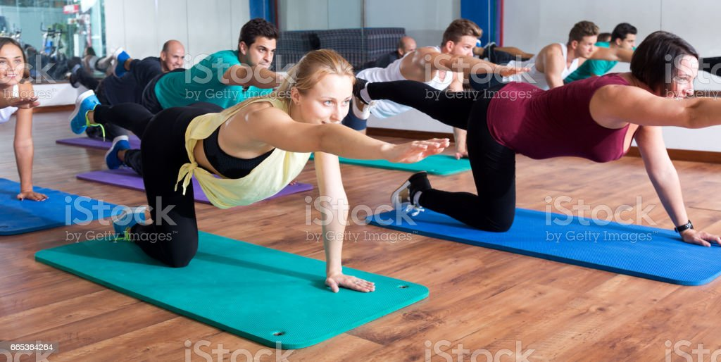 Adults having yoga class in sport club stock photo