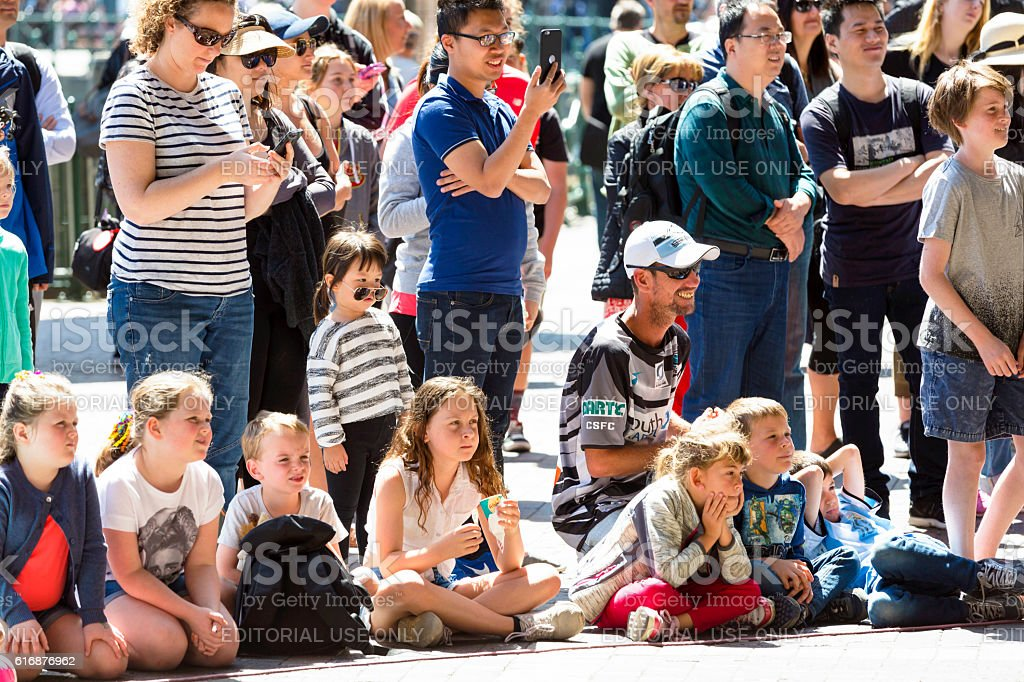 Adults, parents and children watching street performance on sunny day stock photo