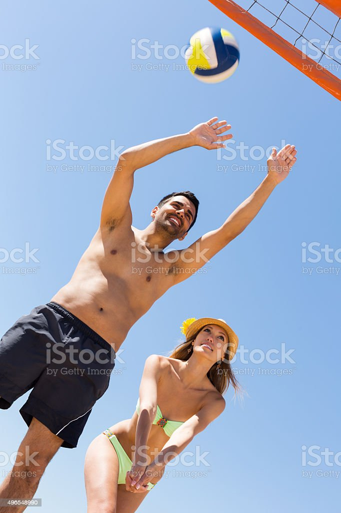 Adults people playing volleyball at beach stock photo