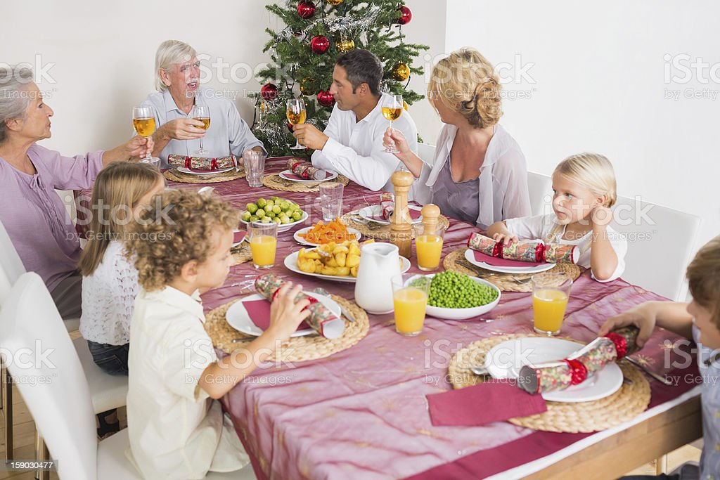 Adults raising their glasses at christmas dinner royalty-free stock photo