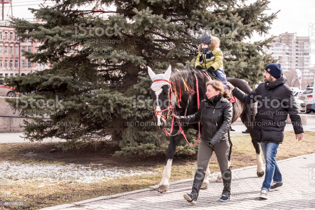 Adults ride with a child on horseback in a park at Carnival stock photo