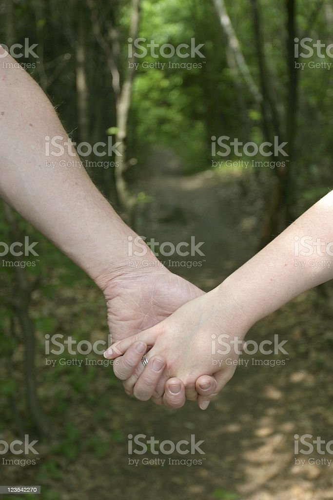 Adults walking through forest royalty-free stock photo