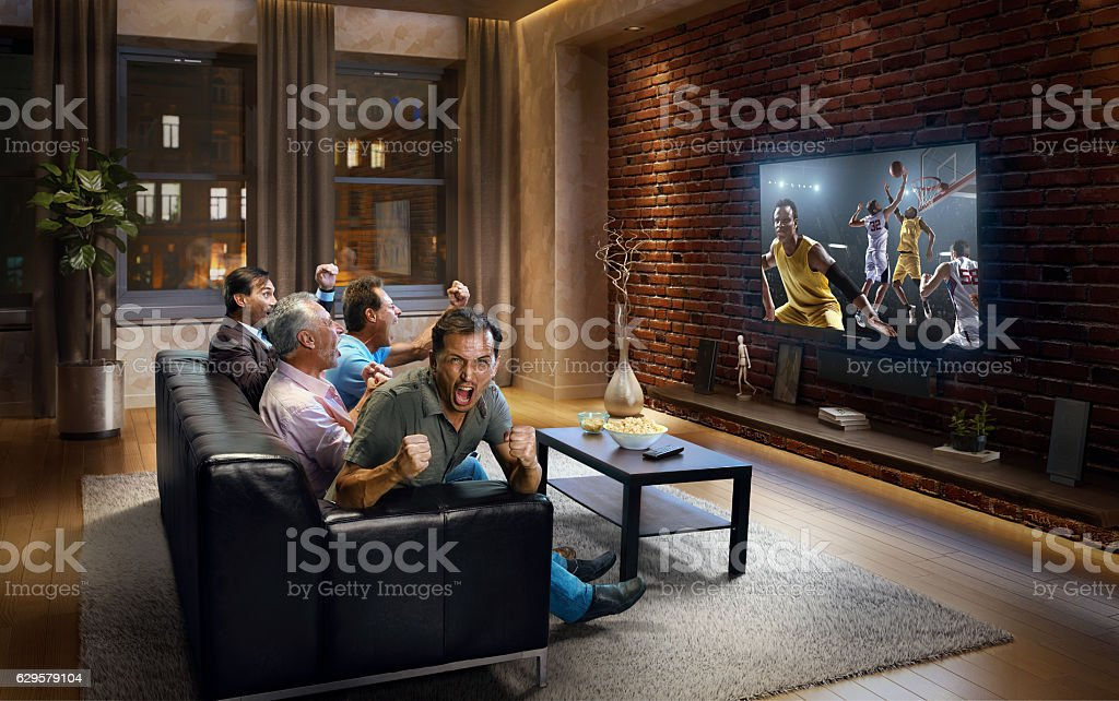 Adults watching  Basketball game at home stock photo