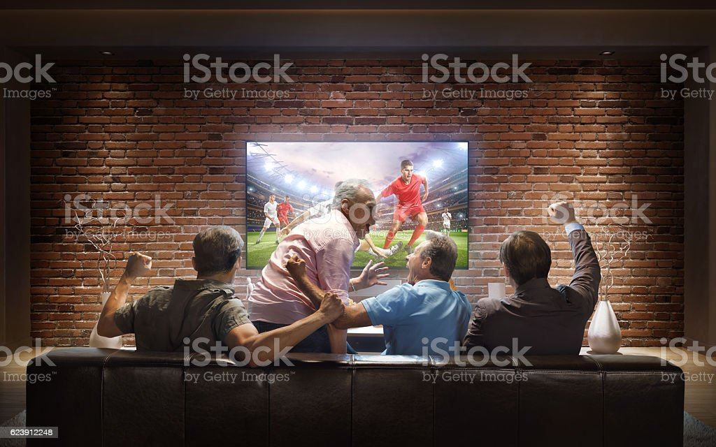 Adults watching Soccer game at home stock photo