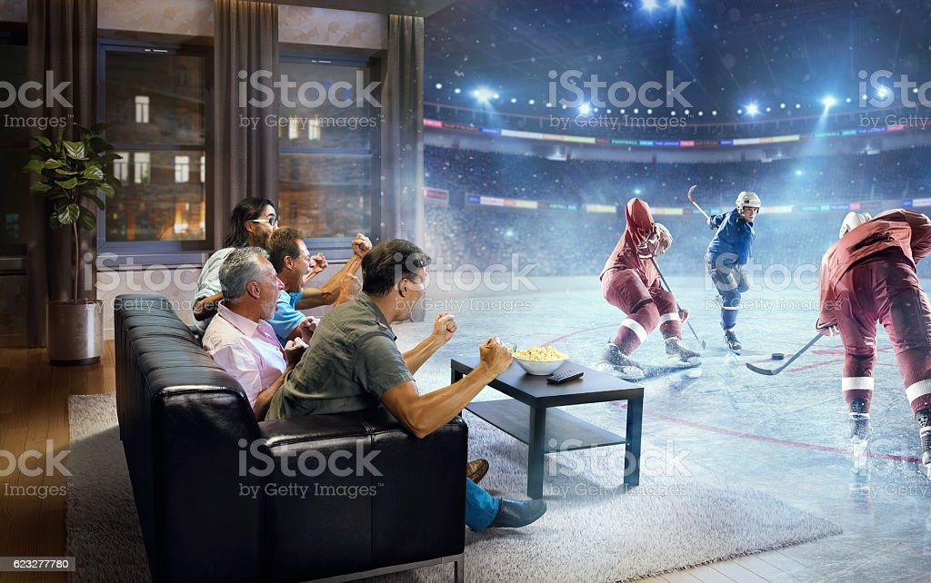 A group of adult male friends are cheering while watching extremely...