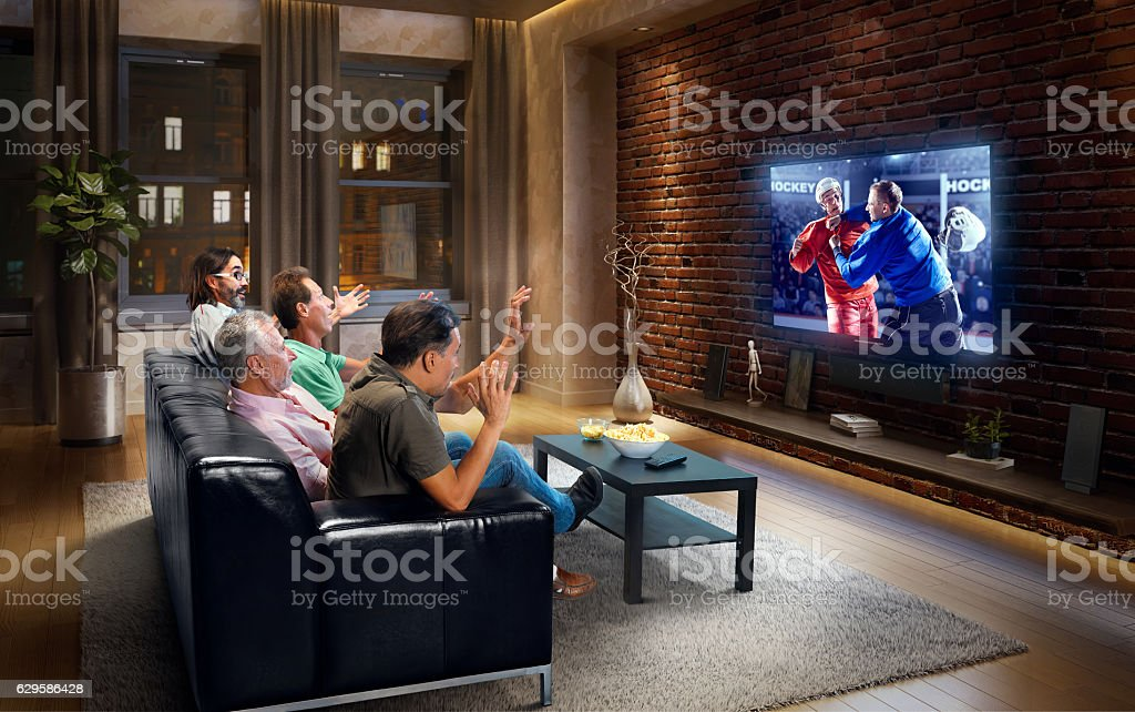 A group of adult male friends are cheering while watching Ice hockey...