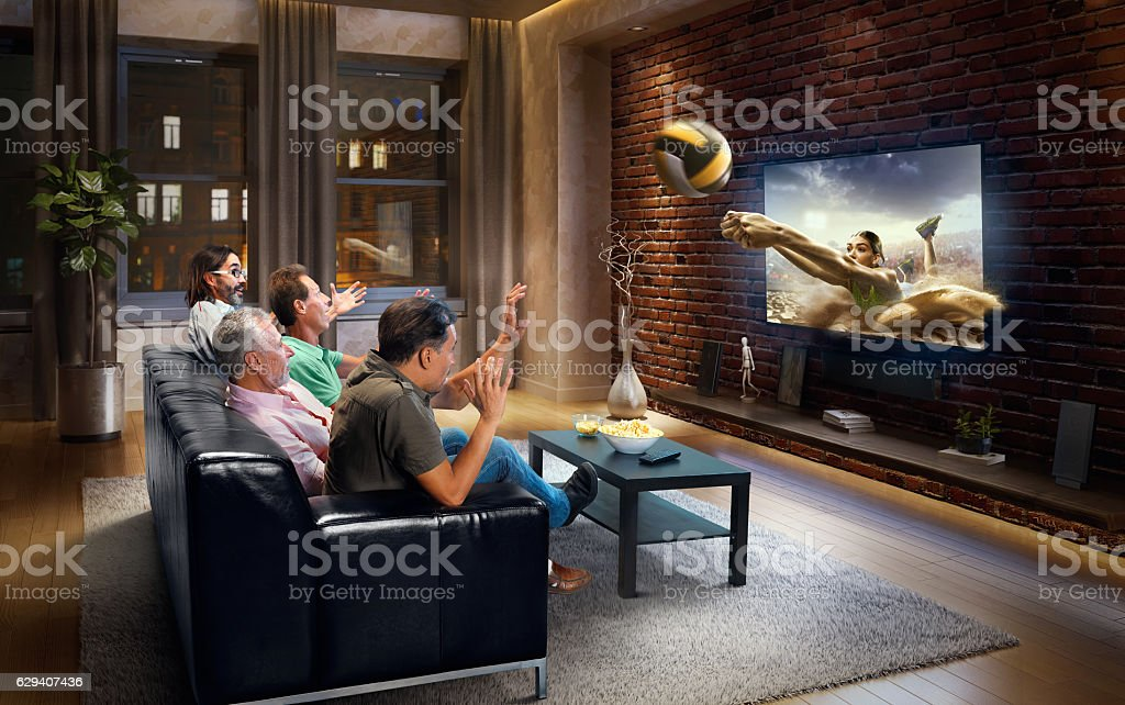 Adults watching Volleyball game at home stock photo