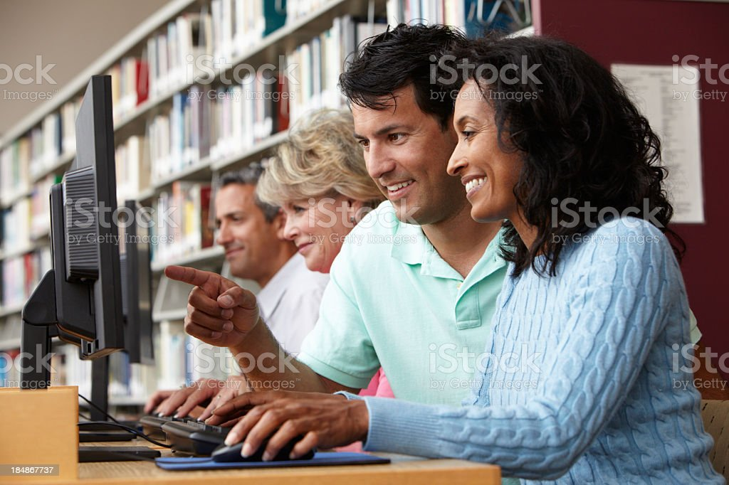 Adults working on computers in a library royalty-free stock photo