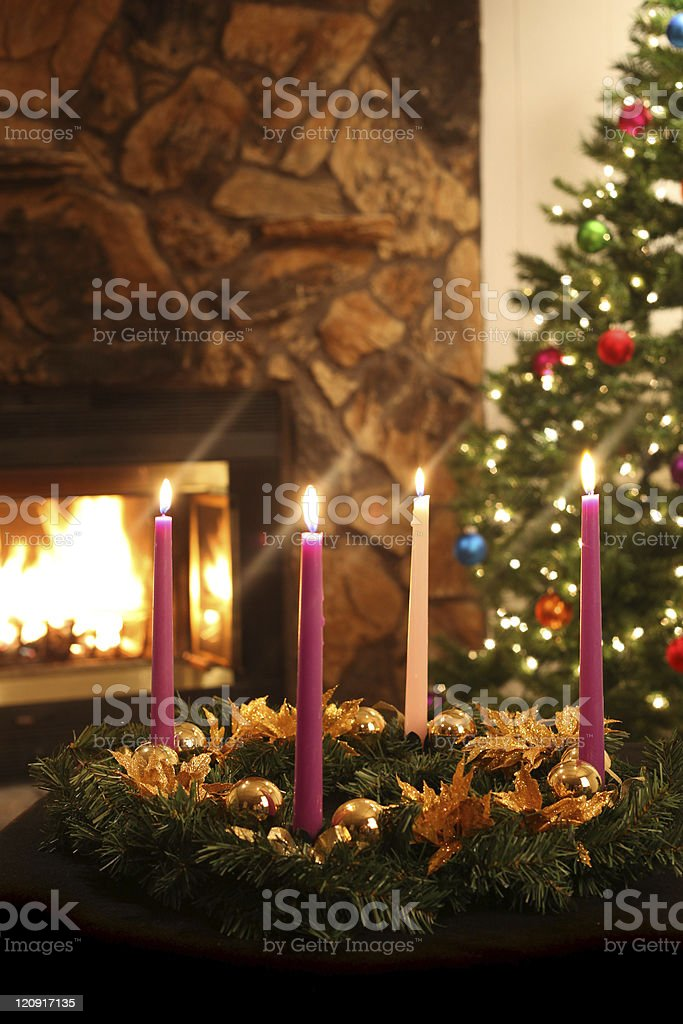 Advent wreath on table with fireplace and tree in background stock photo