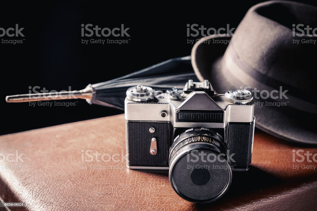 Adventure concept. Old film camera with vintage hat and umbrella on old brown suitcase. Vintage toned stock photo