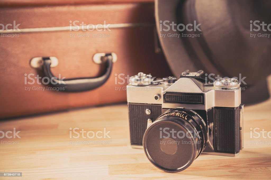 Adventure concept. Old film camera with vintage hat near old suitcase stock photo