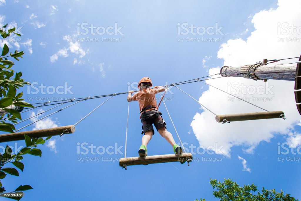Adventure park fun - boy on ropes course stock photo