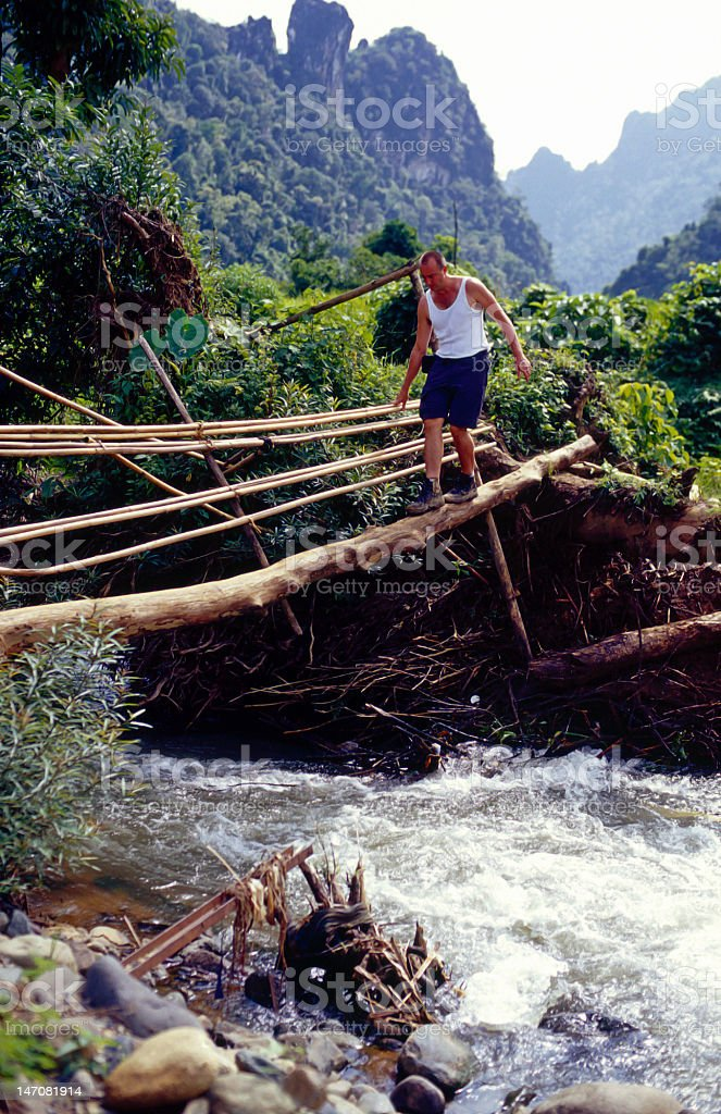 Adventurer crossing a river royalty-free stock photo