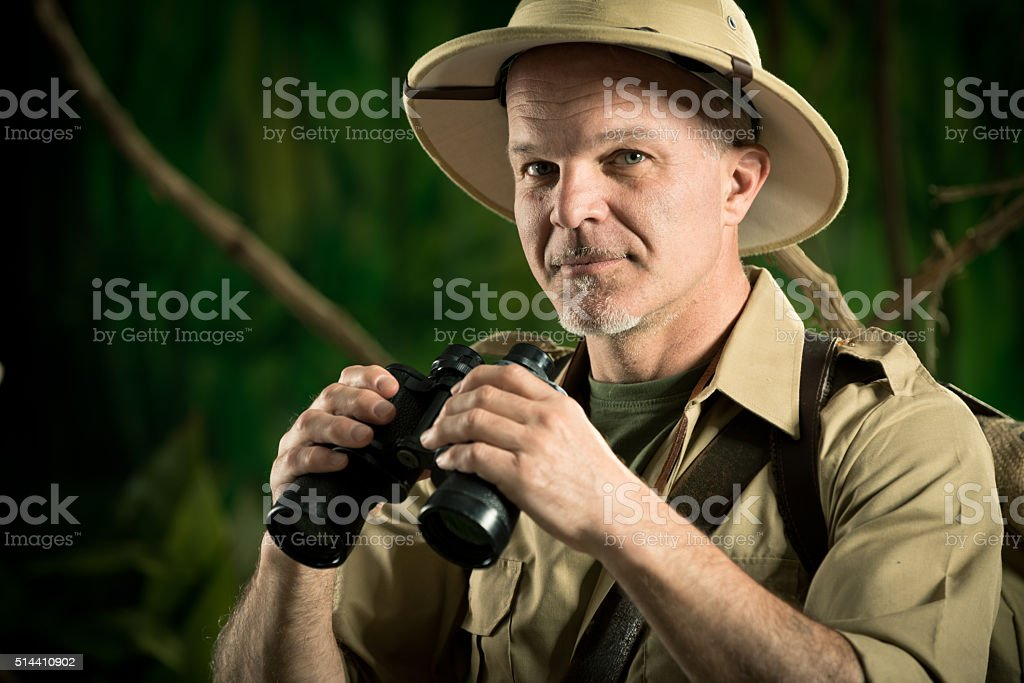 Adventurer in the jungle with binoculars stock photo