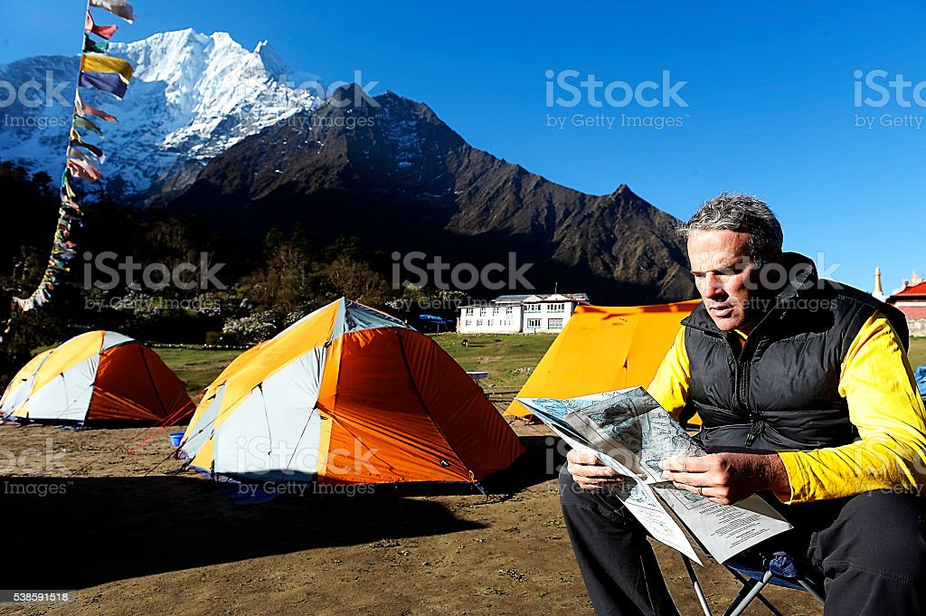 Adventurer reads map with tents and mountains in the background stock photo
