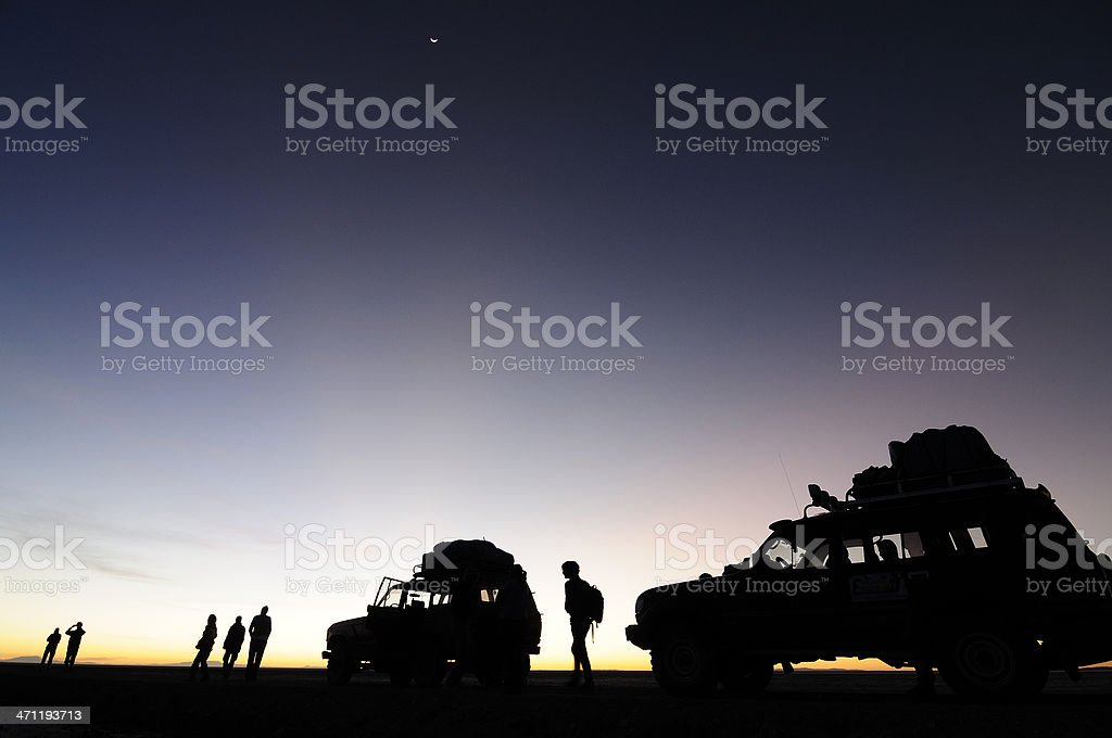 Adventurers at Dawn with Vehicles. stock photo