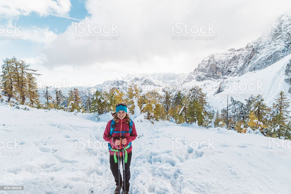 Adventures lady hiking in the mountains covered with snow stock photo