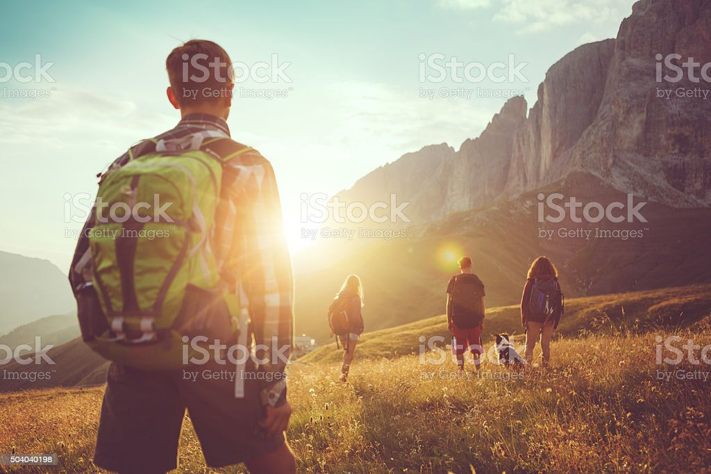 Adventures on the Dolomites: friends hiking with dog stock photo