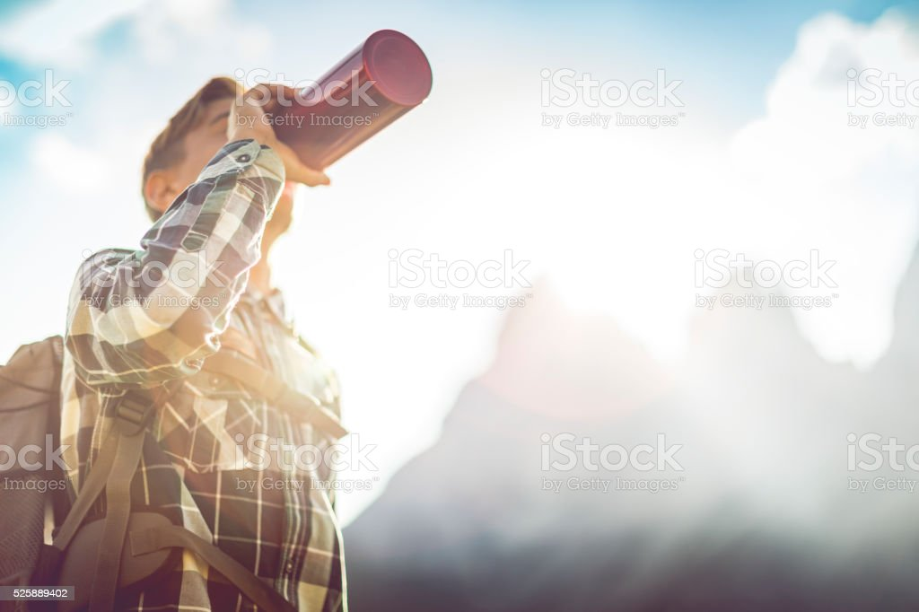 Adventures on the mountain: young backpacker drinks stock photo