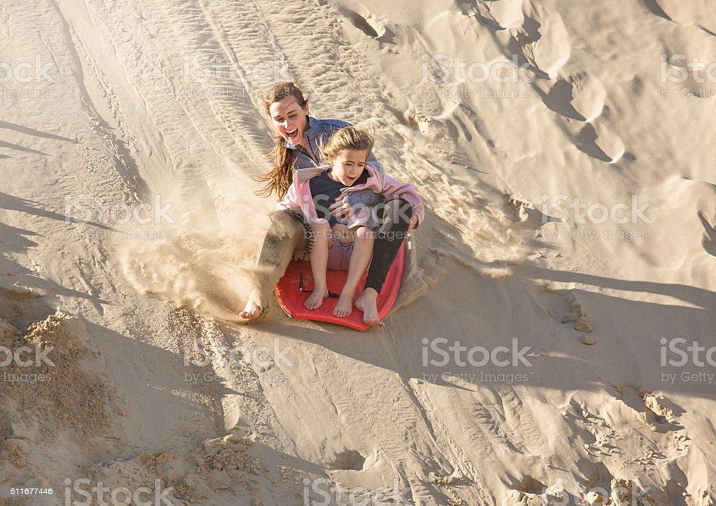 Adventuresome girls boarding down the Sand Dunes stock photo