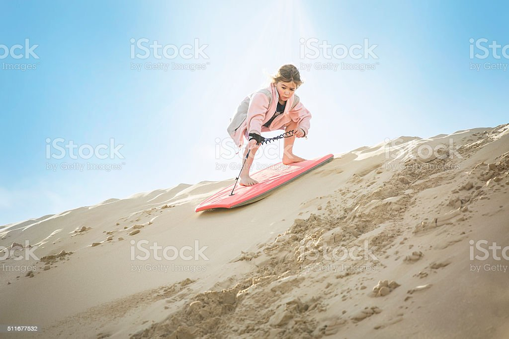 Adventuresome Little Girl boarding down the Sand Dunes stock photo
