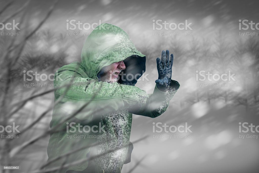 Adventurous man caught in snowstorm or winter blizzard. stock photo
