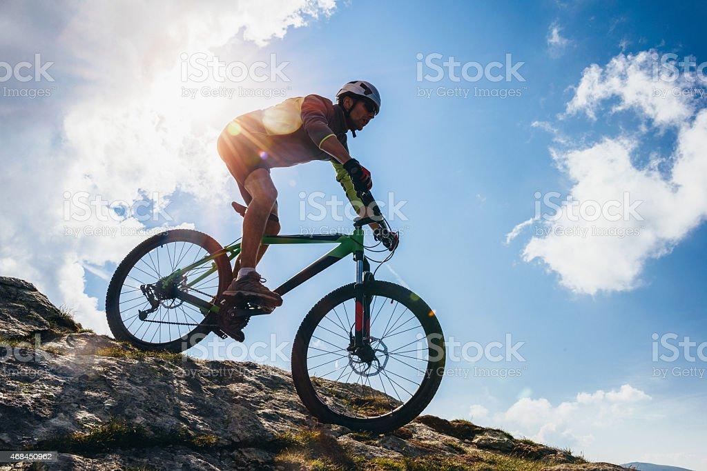 Adventurous Man riding his bike on steep terrain stock photo