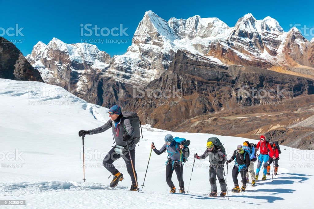 Adventurous People making Ascent to high Mountain walking on Glacier stock photo