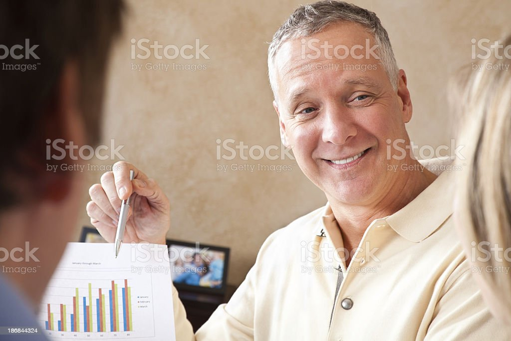 Advisor Showing Financial Charts To Young Couple stock photo