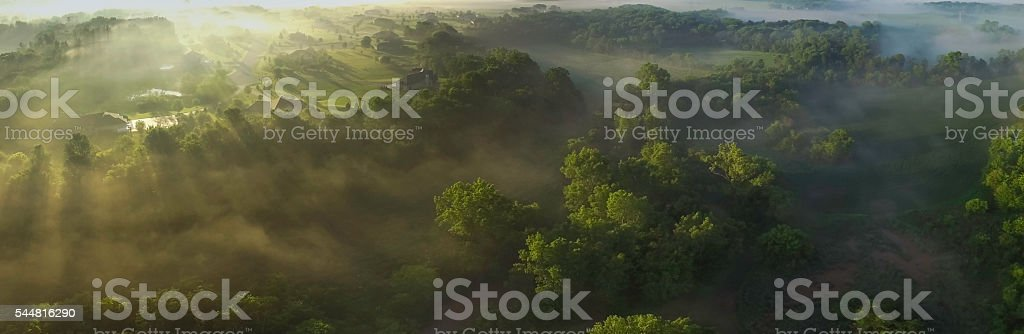 Aerial panorama of foggy valley on edge of town, sunrise stock photo