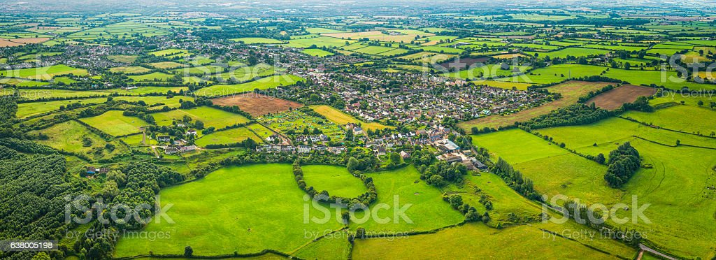 Aerial panorama over country homes surrounded by green patchwork fields stock photo