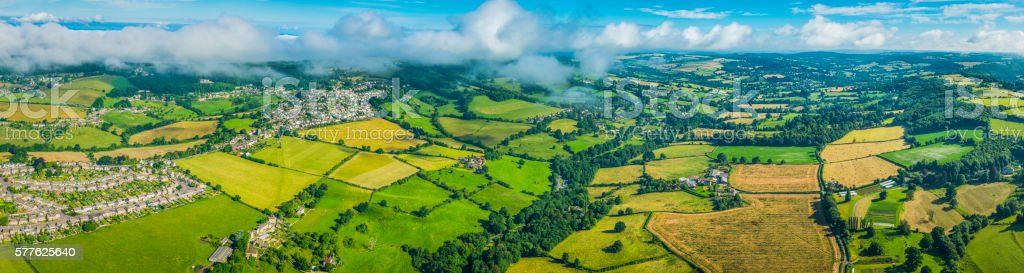 Aerial panorama over country villages farms fields green summer pasture stock photo
