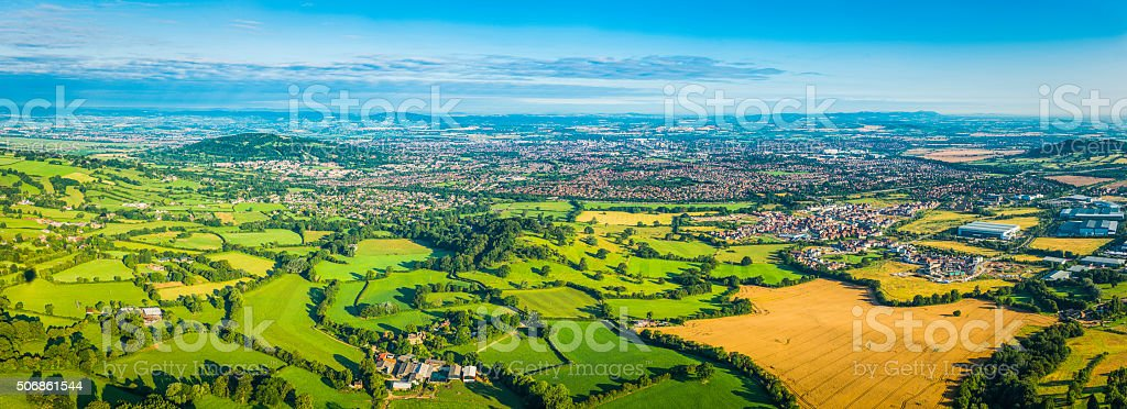 Aerial panorama over green farmland pasture golden crops country town stock photo