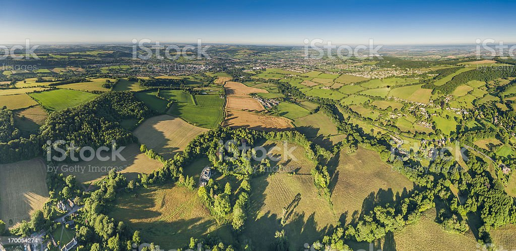 Aerial panorama over green fields country villages blue summer skies royalty-free stock photo