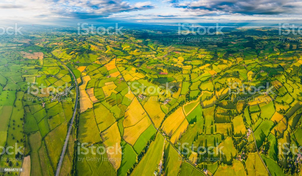 Aerial panorama over green fields country villages farms patchwork pasture stock photo