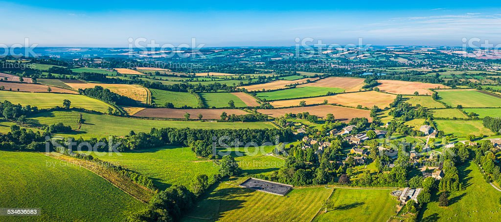 Aerial panorama over green fields farms summer pasture country villages stock photo