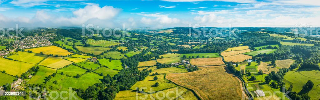 Aerial panorama over green patchwork fields idyllic rural landscape Cotswolds stock photo