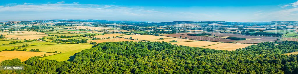 Aerial panorama over idyllic summer countryside patchwork fields woods farms stock photo