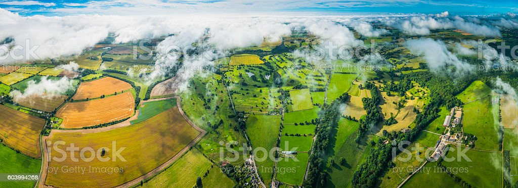 Aerial panorama over patchwork quilt rural landscape fields farms pasture stock photo