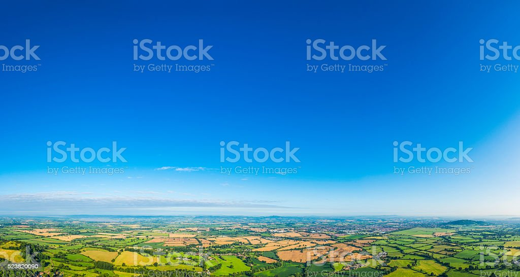 Aerial panorama over picturesque green summer landscape big blue skies stock photo