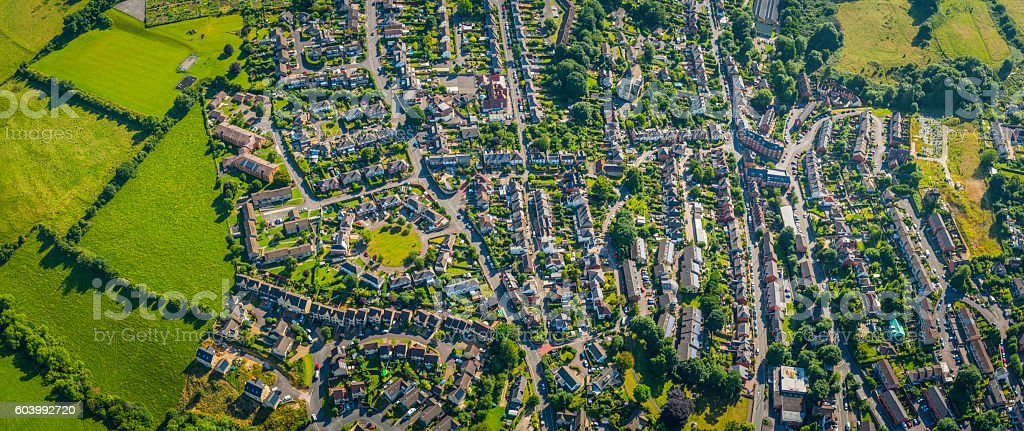 Aerial panorama over suburban homes gardens streets housing green fields stock photo
