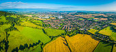 Aerial panorama over summer farmland fields pasture country homes suburbs