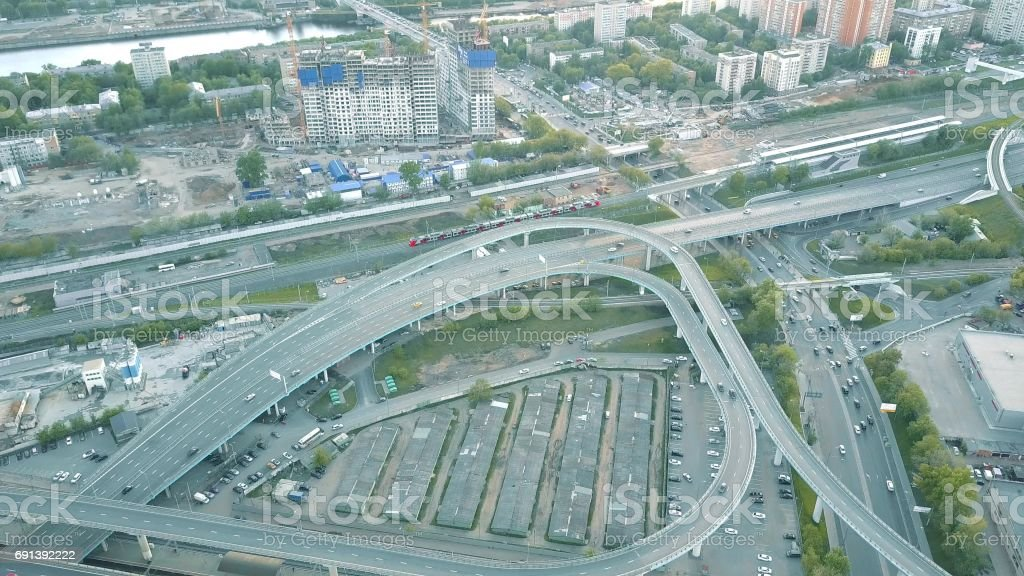 Aerial shot of city road interchange and moving commuter train stock photo