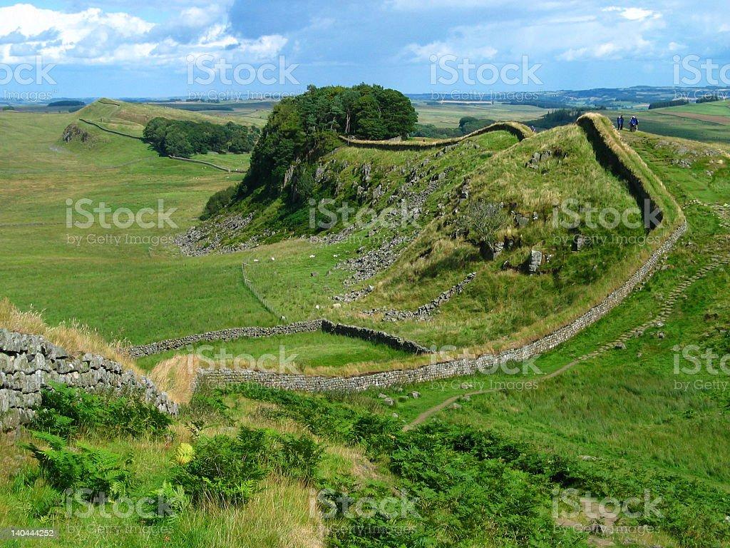 Aerial shot of verdant green field of Hadrian's Wall stock photo