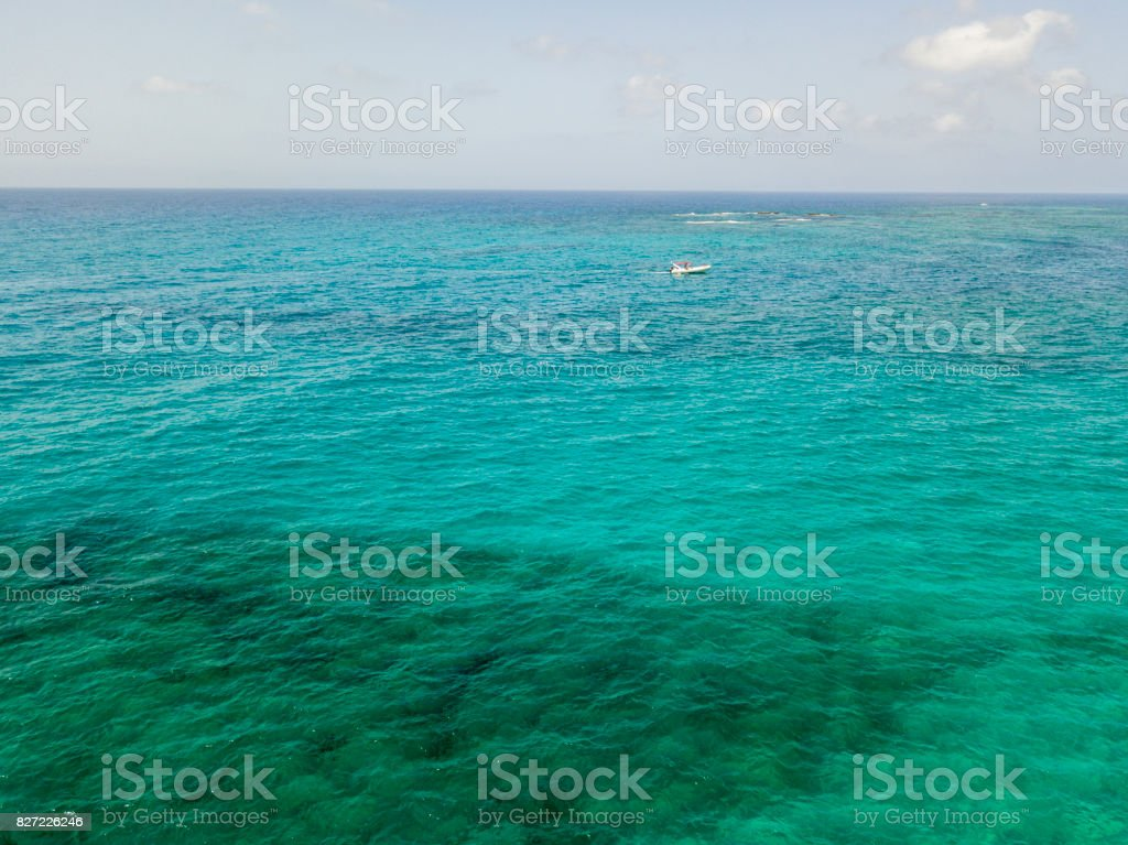 Aerial view of a boat floating on a transparent sea stock photo