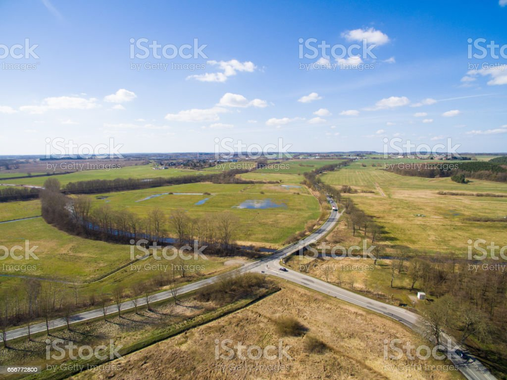 Aerial view of a country road with crossing between agriculture fields and blue sky stock photo
